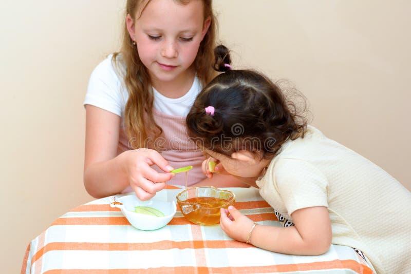 Żydowscy dzieci zamacza jabłko plasterki w miód na Rosh HaShanah zdjęcia royalty free