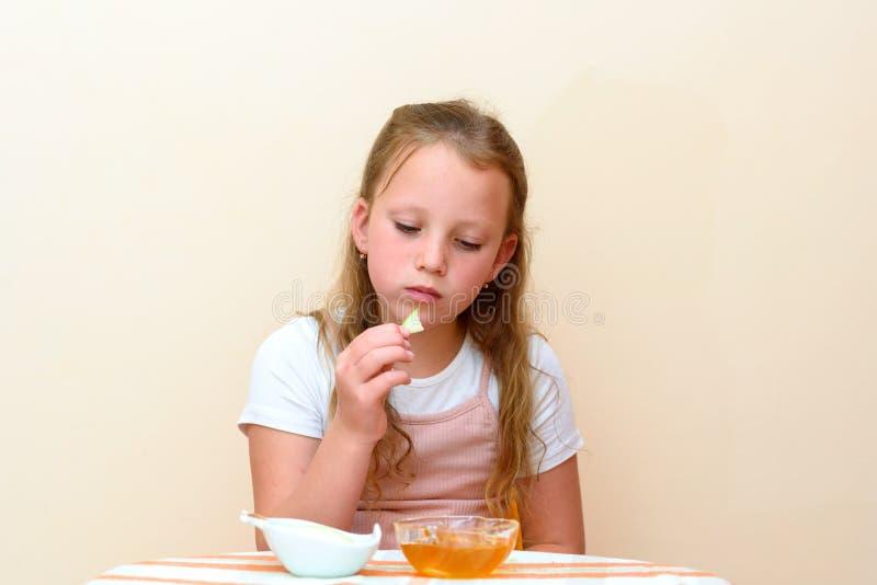 Żydowscy dziecka maczania jabłka plasterki w miód na Rosh HaShanah fotografia stock