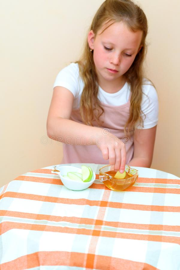 Żydowscy dziewczyny maczania jabłka plasterki w miód na Rosh HaShanah fotografia royalty free