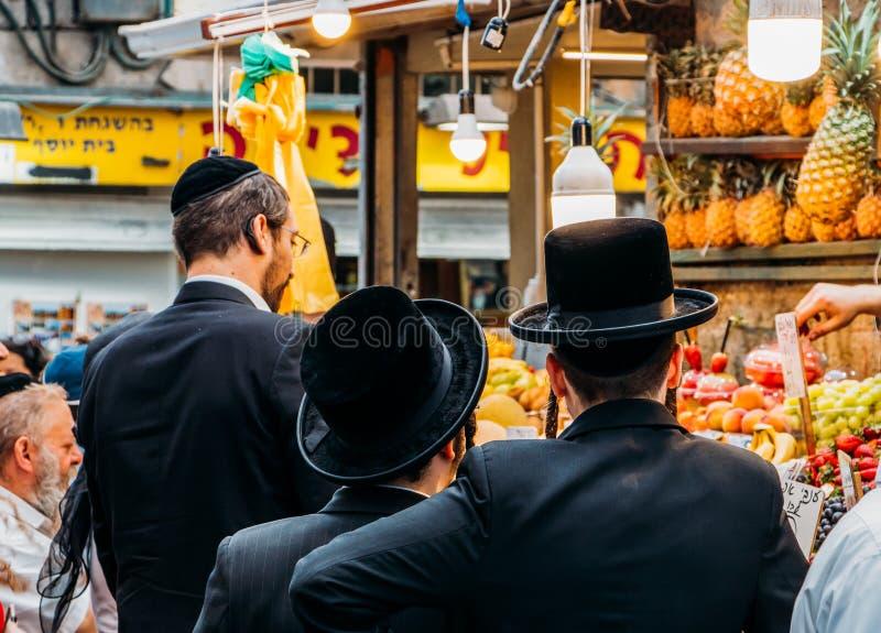 Żydowscy ortodoksów ludzie sprawdzają ananasy przy Jerozolimskim ` s Shruk Machane Yehuda rynkiem który nad 250 kramów karmowym o zdjęcie stock