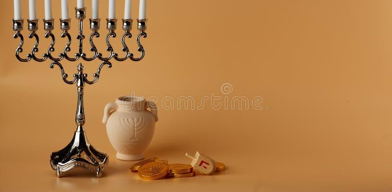 Żydowski wakacyjny Hanukkah tło z menorah, przędzalnianym wierzchołkiem, monetami i dzbankiem, fotografia stock