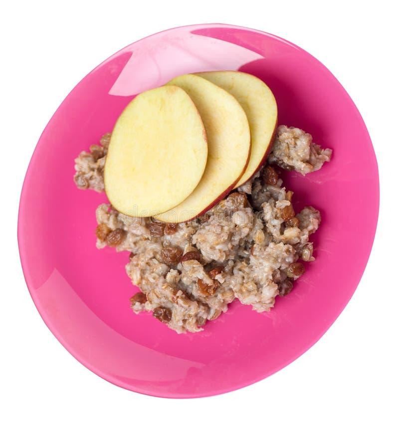 Żyto płatki z rodzynkami i jabłkami na talerzu płatki odizolowywający na białym tle Healty ?niadaniowy Odg?rny widok obraz stock