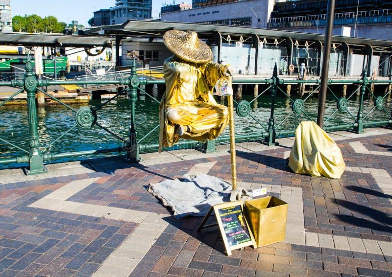 Żywej statuy przedstawienia ` uliczny mistrz lewitaci ` spełnianie w złocistym stroju przy Kółkowym Quay fotografia royalty free