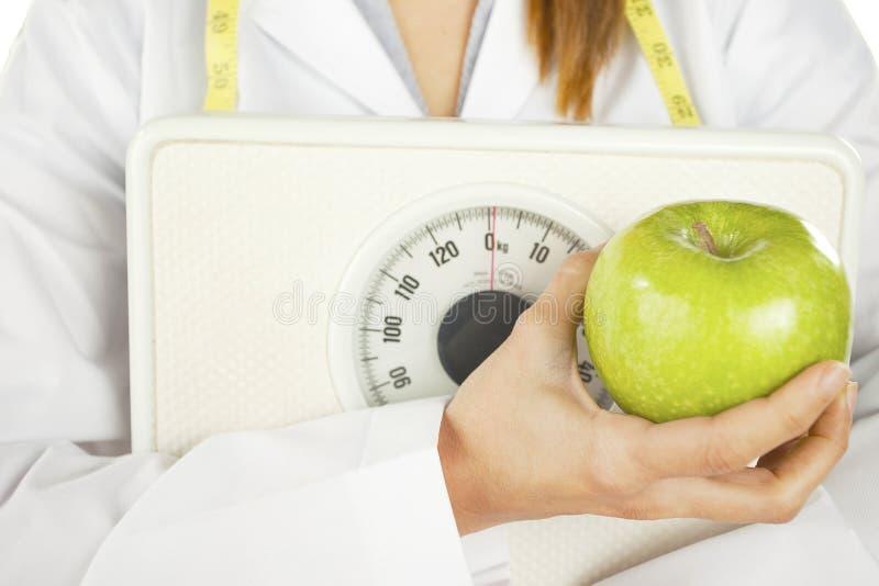 Żywiony mienie zielony ciężar i jabłko waży fotografia stock