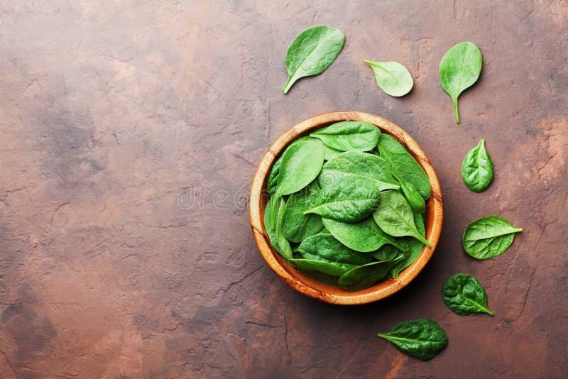 Żywność organiczna Dziecko szpinaka liście w drewnianym pucharze na wieśniaka kamienia stołowym odgórnym widoku Odbitkowa przestr obraz stock