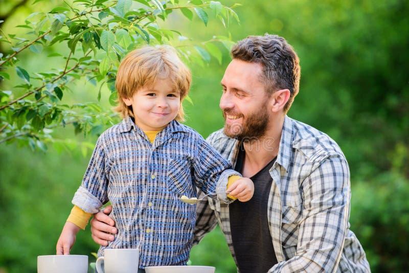 Żywność zdrowa Dzień rodzinny szczęście dziecięce syn i ojciec jedzą mleko owsiane szczęśliwi ojcowie Mały zdjęcia royalty free