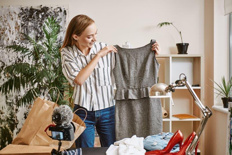 Żywy lać się Młodego żeńskiego blogger wideo magnetofonowy przegląd o klasyk sukni na cyfrowej kamerze w domu fotografia stock