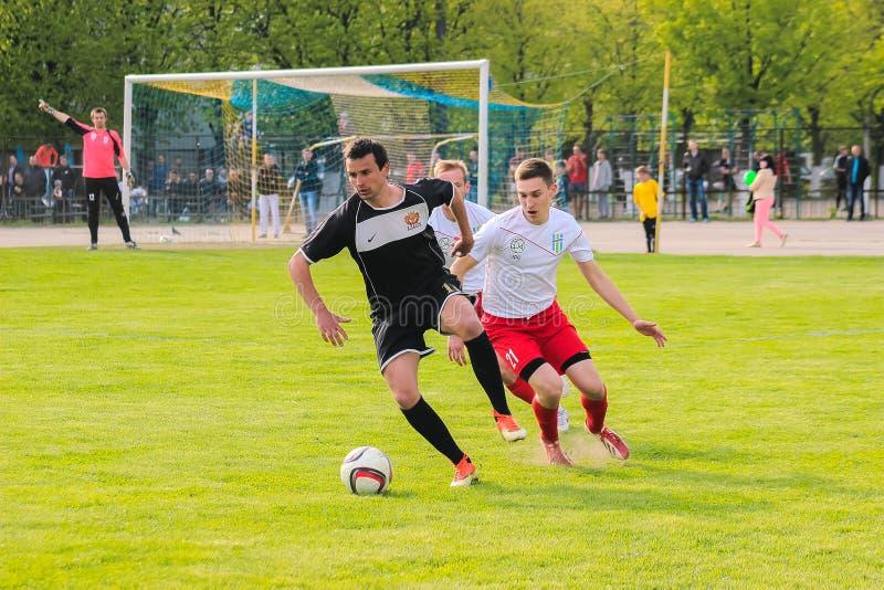 Žytomyr, UCRAINA - 21 maggio 2017: I giocatori di football americano stanno giocando a calcio il gioco di calcio in un campo aper immagini stock libere da diritti