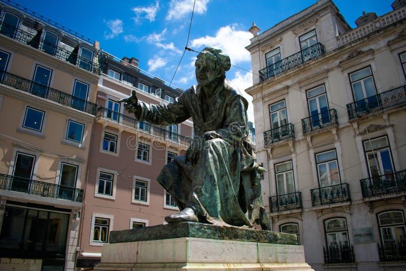 Άγαλμα ή μνημείο του ατόμου ενάντια στα κτήρια στο κέντρο πόλεων του δημοφιλούς τόπου προορισμού τουριστών της Λισσαβώνας στην Πο στοκ εικόνα