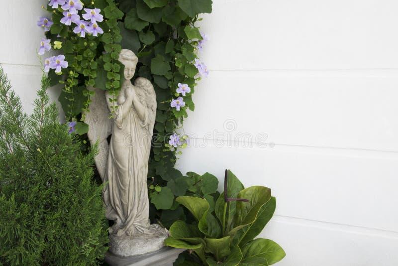 Άγαλμα αγγέλου τσιμέντου με τις διακοσμήσεις εγκαταστάσεων και λουλουδιών gar στοκ εικόνα