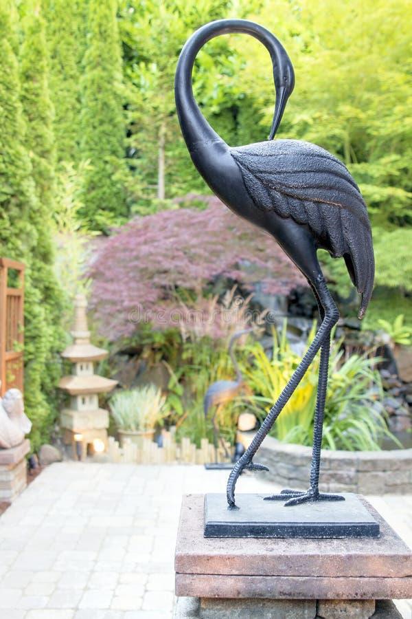 Άγαλμα γερανών χαλκού στον ασιατικό εμπνευσμένο κήπο στοκ φωτογραφία