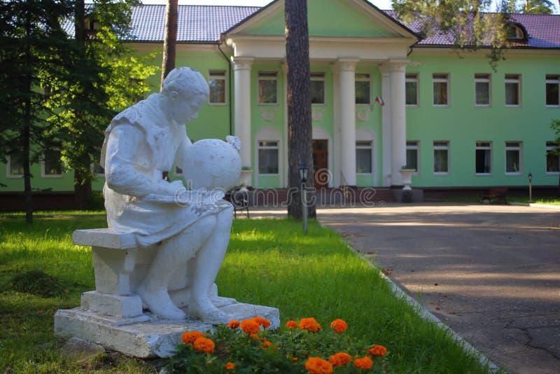 Άγαλμα γύψου μαθήτριας με βιβλίο και υδρόγειο στοκ φωτογραφία