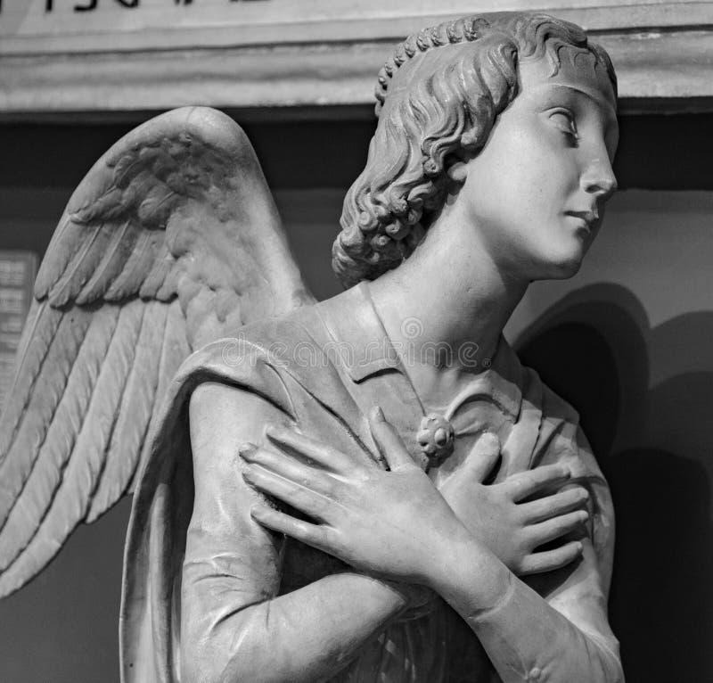 Άγαλμα ενός άσπρου αγγέλου πετρών που προσεύχεται σε ένα νεκροταφείο στοκ φωτογραφία