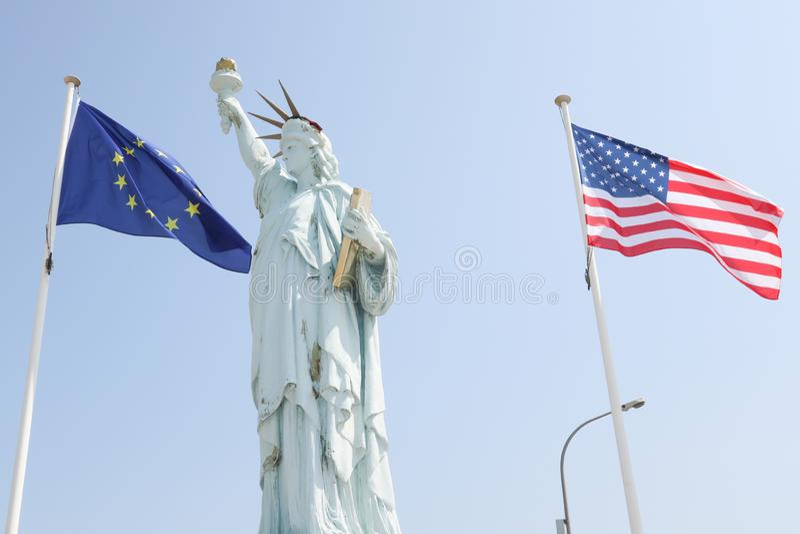 Άγαλμα της ελευθερίας με τις σημαίες της Ευρώπης και των ΗΠΑ στον αέρα στοκ φωτογραφίες