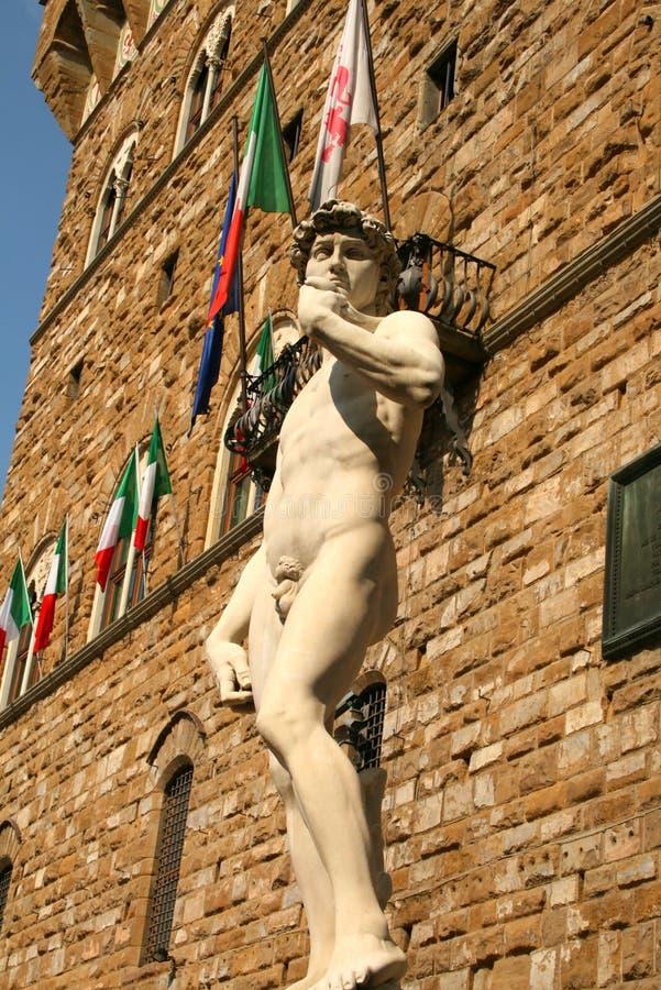 Άγαλμα του Δαβίδ Michelangelo στη Φλωρεντία, Ιταλία - ιταλικές σημαίες στην ανασκόπηση στοκ φωτογραφία