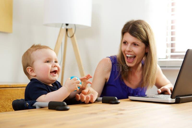 Άγαμη μητέρα που εργάζεται στο lap-top με το αγοράκι της στο σπίτι στοκ φωτογραφίες με δικαίωμα ελεύθερης χρήσης