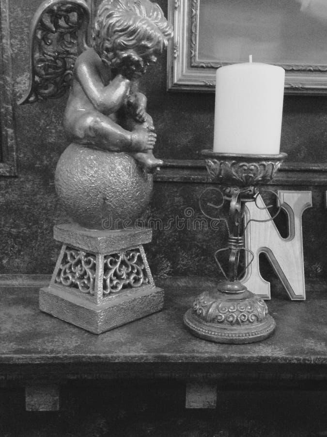 Άγαλμα αγγέλου που εξετάζει ένα κερί σε μια κορνίζα τζακιού εστιών στοκ εικόνα