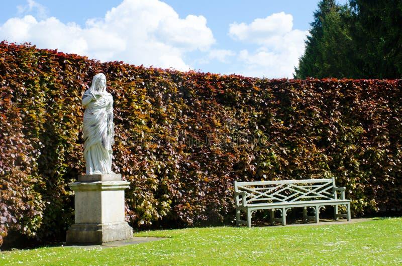 Άγαλμα με τον πάγκο στον αγγλικό κήπο χώρας στοκ εικόνες