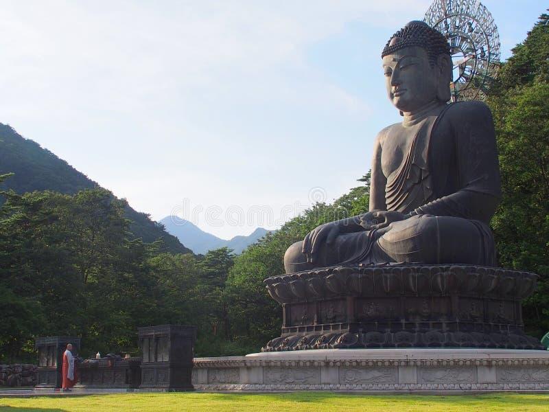 Άγαλμα χαλκού του Βούδα και μοναχός, ναός Sinheungsa, Νότια Κορέα στοκ φωτογραφίες