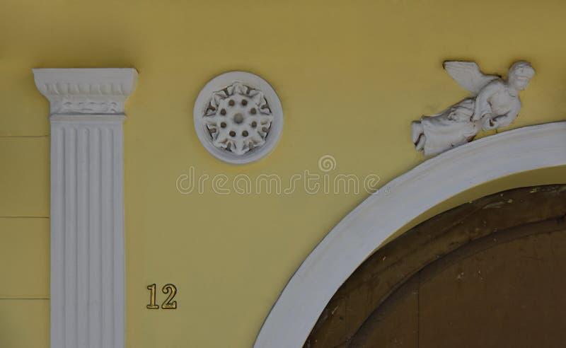 Άγγελος γλυπτός στον ψαμμίτη που διακοσμεί μια πόρτα στοκ φωτογραφία