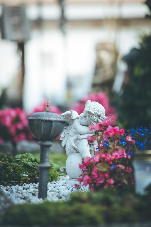 Άγγελος στο νεκροταφείο, τάφος με το ανοικτό βιβλίο από, λουλούδια στοκ φωτογραφία με δικαίωμα ελεύθερης χρήσης
