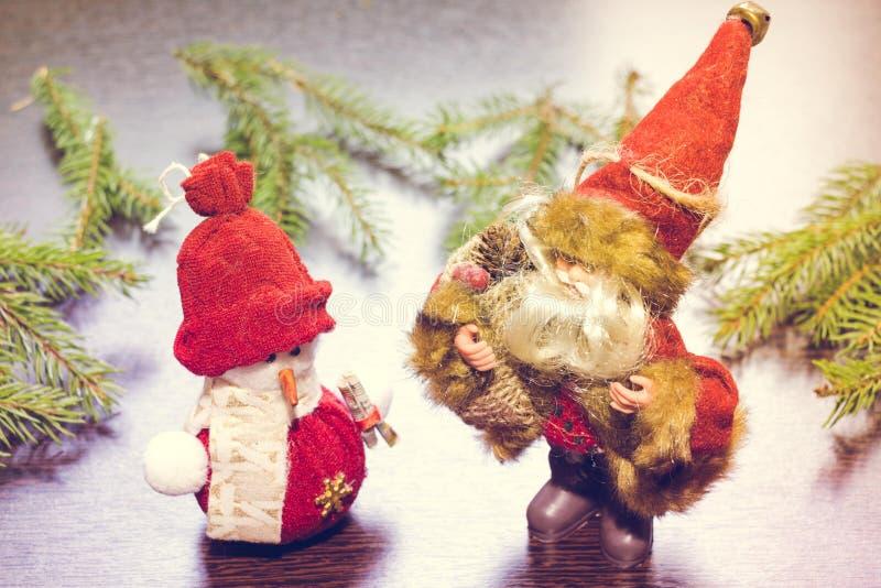 Άγιος Βασίλης ή Άγιος Βασίλης στέκεται δίπλα σε έναν νέο χιονάνθρωπο έτους σε ένα ξύλινο υπόβαθρο με τους κλάδους έλατου στοκ φωτογραφία με δικαίωμα ελεύθερης χρήσης