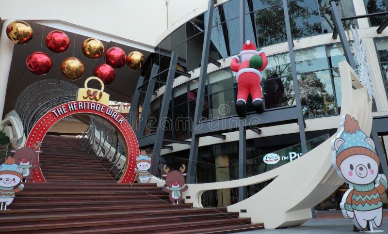 Άγιος Βασίλης αναρριχείται στον τοίχο ενός εμπορικού κέντρου Εορταστικές διακοσμήσεις Χριστουγέννων o στοκ εικόνες