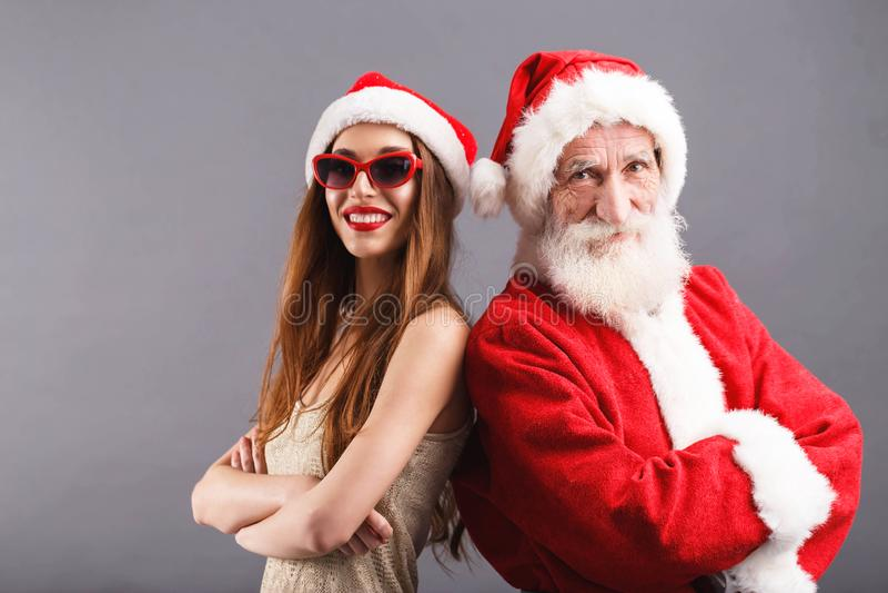 Άγιος Βασίλης και νέα κα Claus που στέκεται και που χαμογελά στο γκρίζο υπόβαθρο στοκ φωτογραφίες