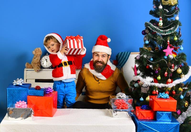 Άγιος Βασίλης και παιδί στο σπίτι Δώρα και κιβώτια Χριστουγέννων στοκ φωτογραφία