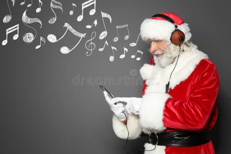 Άγιος Βασίλης με τα ακουστικά, τις σημειώσεις smartphone και μουσικής για το γκρίζο υπόβαθρο, διάστημα για το κείμενο Χριστούγενν στοκ φωτογραφίες