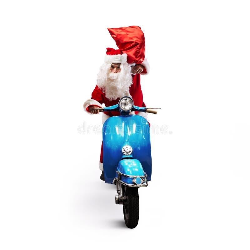 Άγιος Βασίλης με την κόκκινη τσάντα παρουσιάζει σε μια μοτοσικλέτα που παραδίδει παρουσιάζει στοκ εικόνα