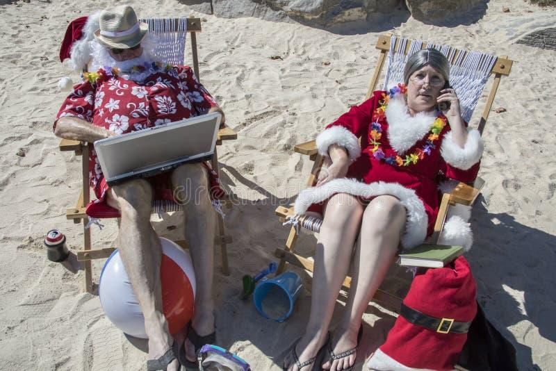 Άγιος Βασίλης στο φορητό προσωπικό υπολογιστή και κα Claus στο τηλέφωνο στο αμμώδες β στοκ εικόνες