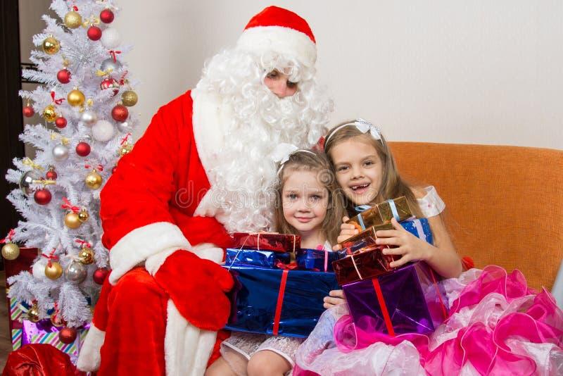 Άγιος Βασίλης έδωσε παρουσιάζει στα παιδιά και αγκαλιασμένος στοκ εικόνες