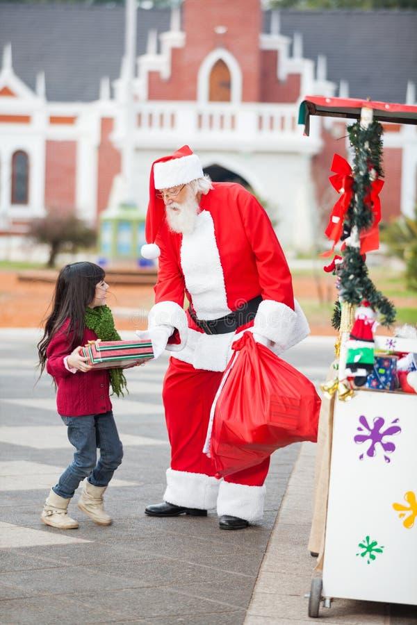 Άγιος Βασίλης που δίνει το δώρο στο κορίτσι στοκ φωτογραφία με δικαίωμα ελεύθερης χρήσης
