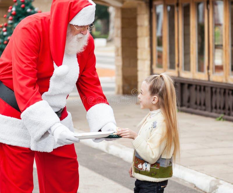 Άγιος Βασίλης που προσφέρει τα μπισκότα στο κορίτσι στοκ εικόνες με δικαίωμα ελεύθερης χρήσης