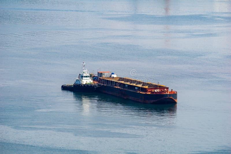 Άγκυρες φορτηγίδων μαζικού φορτίου με μια tugboat πρόσδεση στην πλευρά του Bul στοκ φωτογραφία με δικαίωμα ελεύθερης χρήσης