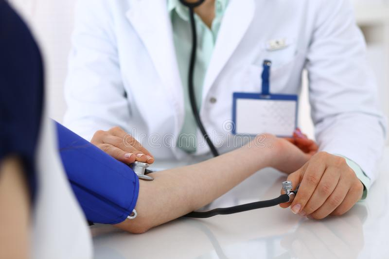 Άγνωστη γυναίκα γιατρών που ελέγχει τη πίεση του αίματος του θηλυκού ασθενή, κινηματογράφηση σε πρώτο πλάνο Καρδιολογία στην ιατρ στοκ φωτογραφία