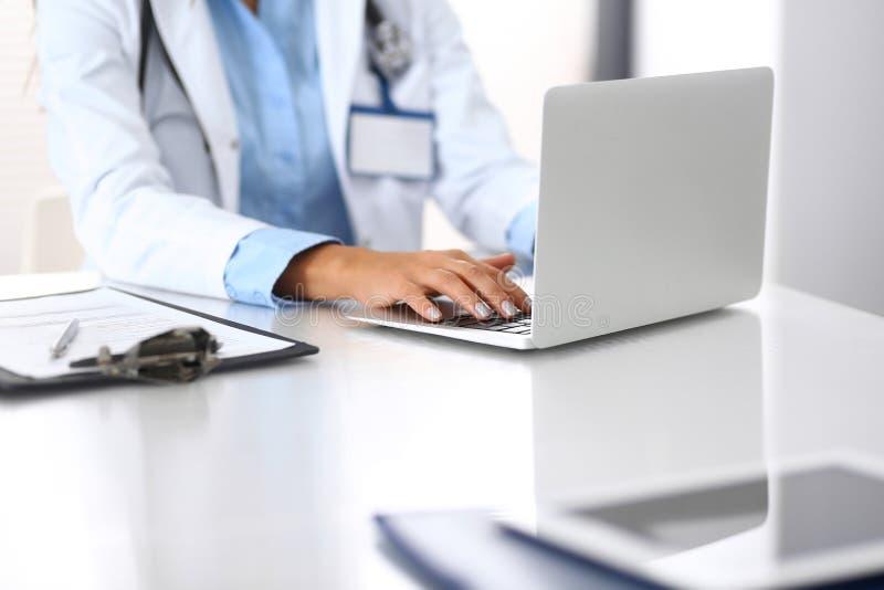 Άγνωστη δακτυλογράφηση γυναικών γιατρών στο φορητό προσωπικό υπολογιστή καθμένος στο γραφείο στο γραφείο νοσοκομείων στενά χέρια  στοκ φωτογραφία με δικαίωμα ελεύθερης χρήσης