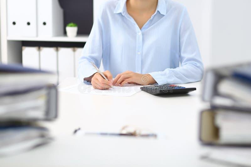 Άγνωστος θηλυκός λογιστής ή οικονομικός επιθεωρητής που υπολογίζει ή που ελέγχει την ισορροπία, που κάνει την έκθεση, κινηματογρά στοκ εικόνα