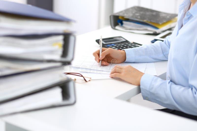 Άγνωστος θηλυκός λογιστής ή οικονομικός επιθεωρητής που υπολογίζει ή που ελέγχει την ισορροπία, που κάνει την έκθεση, κινηματογρά στοκ εικόνα με δικαίωμα ελεύθερης χρήσης