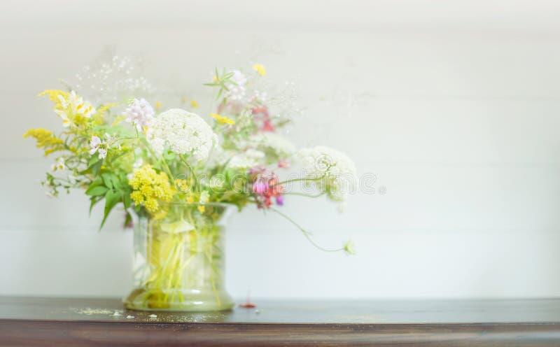 Άγρια δέσμη λουλουδιών στο δοχείο γυαλιού στο ξύλινο ράφι στο ελαφρύ υπόβαθρο Floral εγχώρια διακόσμηση στοκ εικόνες