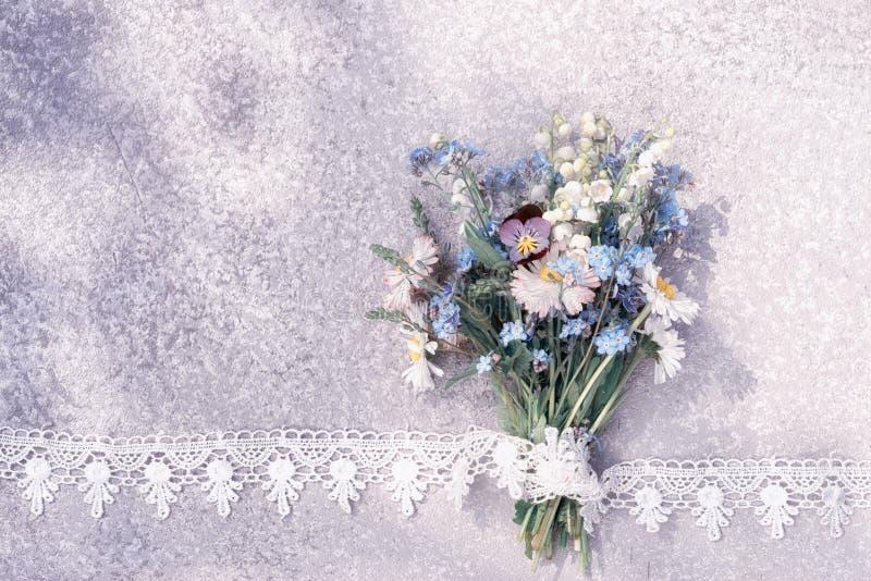 Άγρια ανθοδέσμη λουλουδιών που βάζει σε έναν παλαιό αγροτικό ασημένιο πίνακα στο πλαίσιο δαντελλών στοκ εικόνα