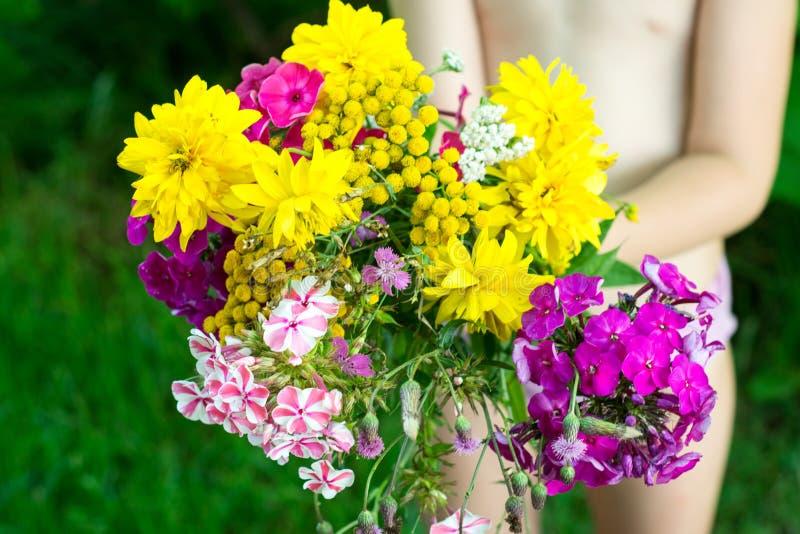 Άγρια ανθοδέσμη λουλουδιών στα χέρια παιδιών στοκ εικόνες με δικαίωμα ελεύθερης χρήσης