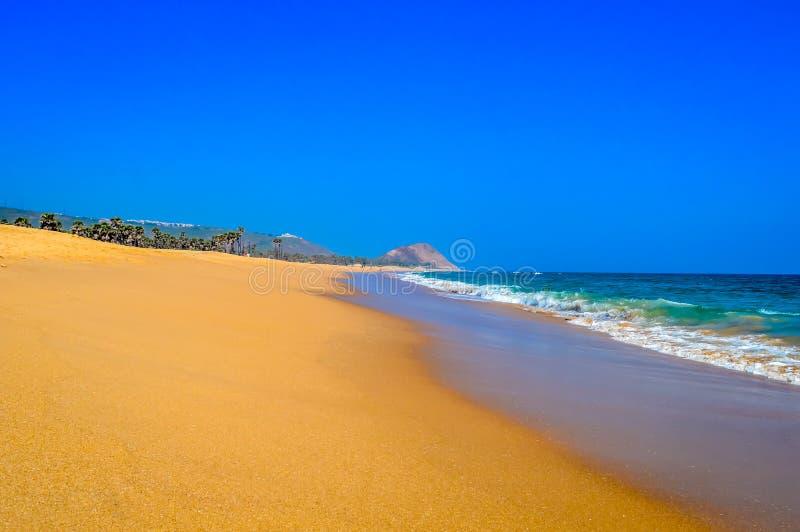 Άγρια κενή τροπική παραλία, δονούμενη κίτρινη άμμος, φωτεινός μπλε ουρανός, κρύσταλλο - σαφή νερά με το νερό που συντρίβει στην α στοκ εικόνα με δικαίωμα ελεύθερης χρήσης