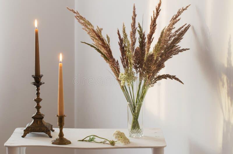 Άγρια λουλούδια ανθοδεσμών και καίγοντας κεριά στον ήλιο στο άσπρο ι στοκ εικόνα