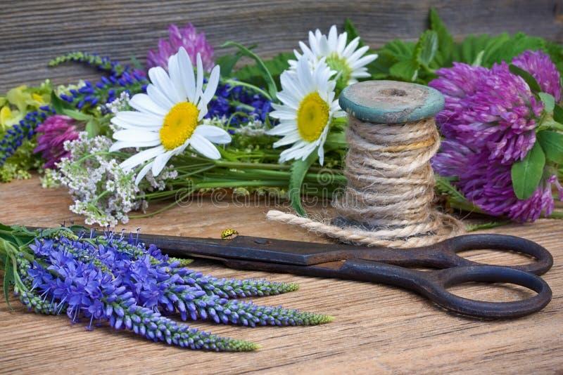 Άγριες λουλούδια, ψαλίδι και δεσμίδα των νημάτων σε μια παλαιά ξύλινη πλάτη στοκ φωτογραφία