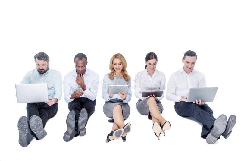 Άγρυπνοι συνάδελφοι που εργάζονται στις συσκευές τους στοκ εικόνα με δικαίωμα ελεύθερης χρήσης