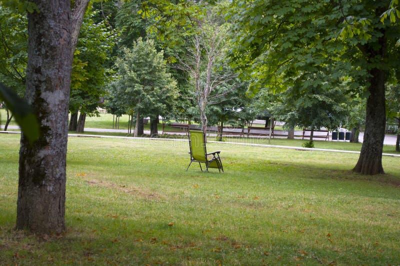 Άδεια καρέκλα στέκεται στο γρασίδι στο πάρκο στοκ φωτογραφία με δικαίωμα ελεύθερης χρήσης
