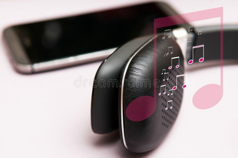 Άκουσμα τη μουσική στα ακουστικά με τη μουσική γραφική παράσταση συμβόλων σημειώσεων στοκ εικόνες