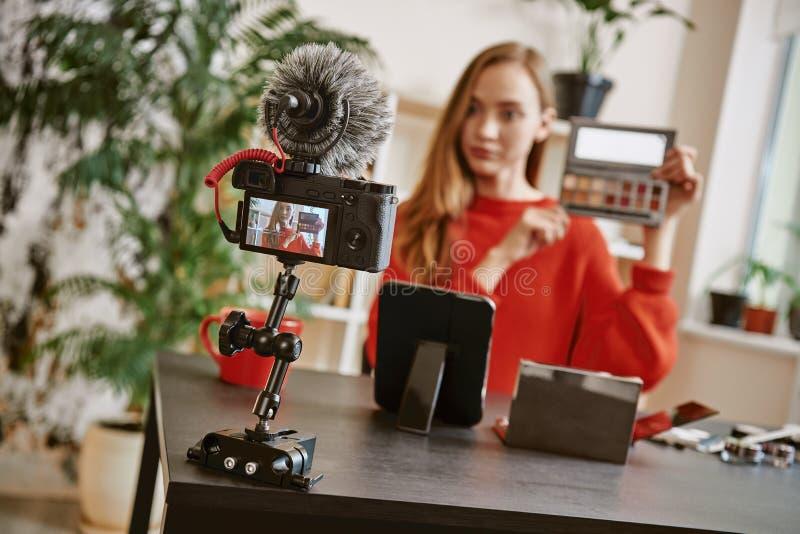 Άκρες ομορφιάς Νέα ελκυστική γυναίκα που παρουσιάζει παλέτα makeup στη κάμερα καταγράφοντας την τηλεοπτική αναθεώρηση για την ομο στοκ φωτογραφία